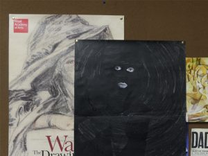 A mostly black drawing with cutout eyes and mouth, taped over exhibition posters in the History of Art building