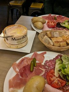 Cheese, salad, meats laid out on a table