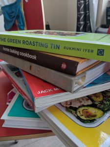 A pile of cookbooks on a kitchen chair