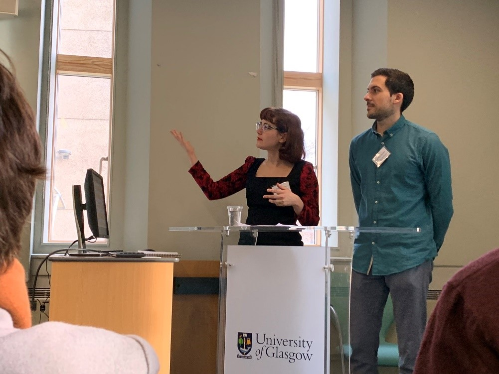 A woman and a man standing at a podium with University of Glasgow written on it. The woman is gesturing to something off camera.