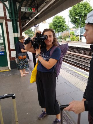 Ally holding a video camera on a tube platform