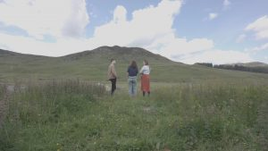 Three people standing in a field with hills behind