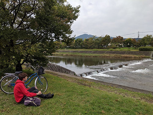 A boy in a red sweatshirt with a blue bike sitting next to the Kamo River near Kyoto University.