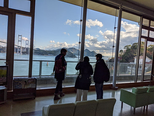 A view of the Akashi Kaikyo Bridge through a large glass window with three people standing in front of it
