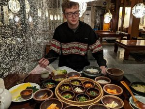 Callum sitting in a restaurant with lots of different Korean vegetarian dishes on the table in front of him.